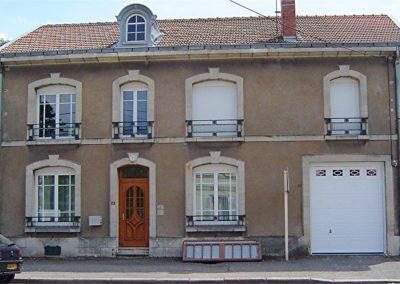 maison fenêtres PVC porte dentrée bois et porte de garage sectionnelle à cassettes